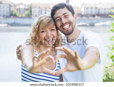 Couple in love outside showing heart with fingers - stock photo