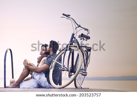 Couple in love resting on a boardwalk with a bike at the lake - stock photo