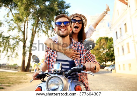 Couple in love riding a motorbike , Handsome guy and young sexy woman travel . Young riders  enjoying themselves on trip. Adventure and vacations concept. - stock photo