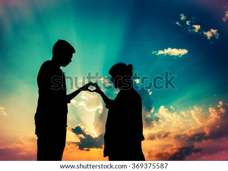 Couple in love silhouette during sunset - touching hands in heart shape with sunray god light background , valentine background - stock photo