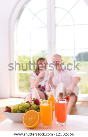 Couple in love sitting on the floor / focus on the fresh juices and fruits - stock photo