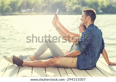 Couple in love sitting on the pier, selfie - stock photo