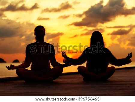 couple in love sitting on the sea and is engaged in yoga - stock photo