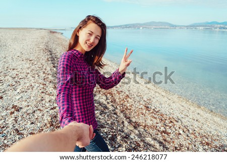 Couple in love. Smiling young woman holding man's hand and showing peace sign on beach near the sea. Point of view shot - stock photo