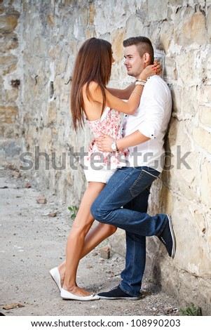 Couple in love standing in front of a stone wall - stock photo