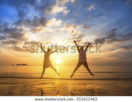 Couple in love to jump up on the beach during a stunning sunset. - stock photo