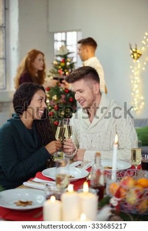 couple in love toasting with champagne while celebrating christmas with friends - stock photo