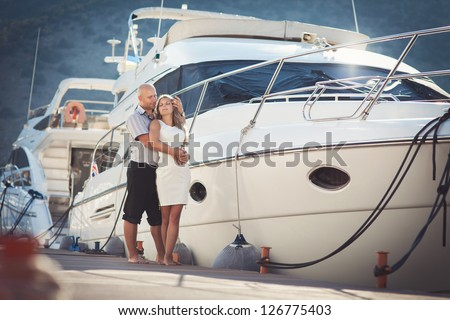 couple in love together near sea and yacht enjoy moment of happiness at honeymoon. Playful family at vacation. handsome man and beautiful woman having fun. Girlfriend and boyfriend on date near ocean. - stock photo