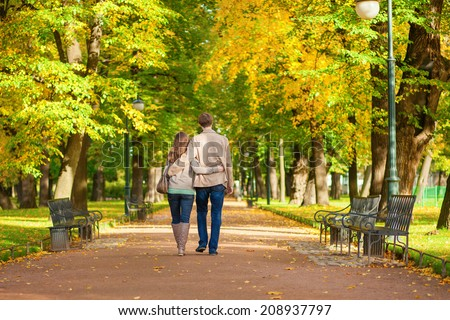 Couple in love walking together in park on a fall day - stock photo