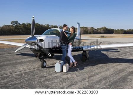 Couple in love with luggage and private plane - stock photo