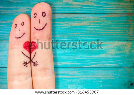 Couple in love with painted smiley and hugging - stock photo