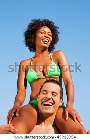 Couple in love - Woman of Brazilian origin in bikini sitting on her man's shoulders under blue sky - summer and fun - stock photo