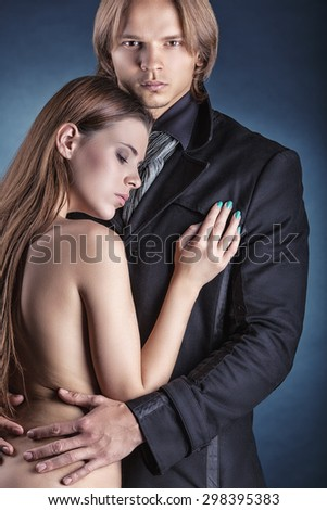 Couple in love. Young business man with a naked woman on a dark background - stock photo