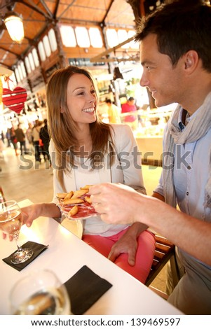 Couple in Madrid eating spanish savouries - stock photo