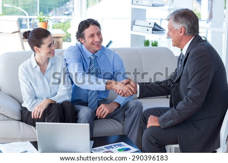 Couple in meeting with a financial adviser in living room - stock photo