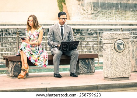 Couple in moment of disinterest  - Break up concept and new technologies addiction - Business man at laptop ignoring girlfriend texting sms with smartphone - Neutral color tone due to the cloudy day - stock photo