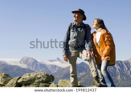 Couple in mountains, man standing, woman sitting on rocks - stock photo