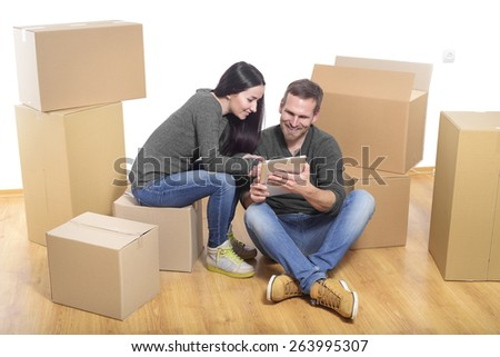Couple in new home between the boxes, with a Tablet PC in the hands. - stock photo