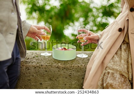 Couple in Paris, eating macaroons and drinking champagne - stock photo