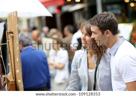 Couple in Paris looking at paintings in the street - stock photo