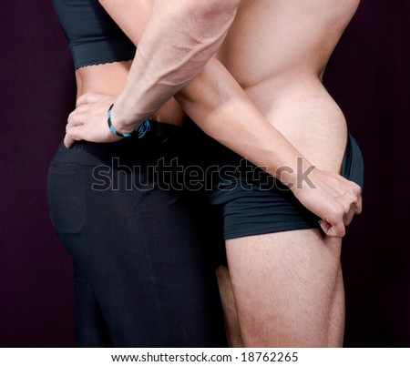 couple in passionate embrace and undressing each other during sexual foreplay - stock photo