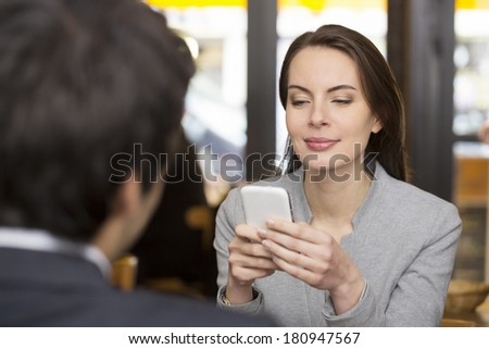 Couple in restaurant, woman is on the phone, sms, surfing web - stock photo