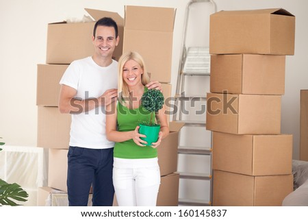 Couple in room full of cardboard boxes, while moving house - stock photo