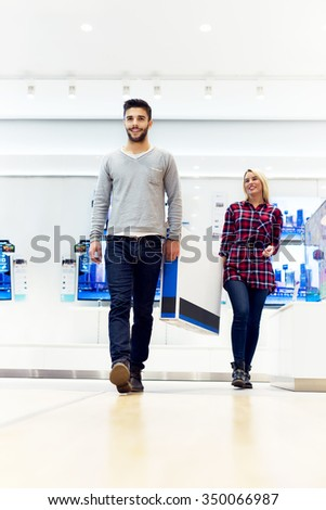 Couple in shopping at TV store. They are walking and holding big unpacked tv. Shallow depth of field. Selective focus on him. - stock photo