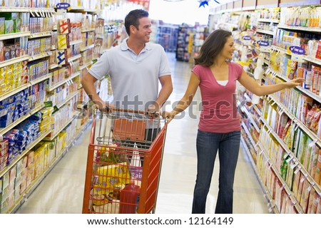 Couple in shopping in supermarket grocery aisle - stock photo
