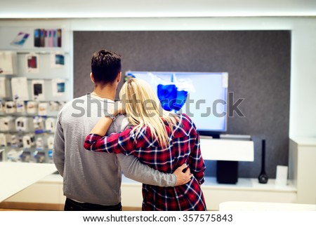 Couple in shopping, looking for a new tv. Shallow depth of field. - stock photo