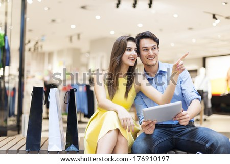 Couple in shopping mall using digital tablet  - stock photo