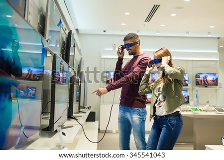 Couple in shopping. They are looking for new 3D tv. They are holding 3D glasses and watching tv. Shallow depth of field. Very natural lighting. - stock photo