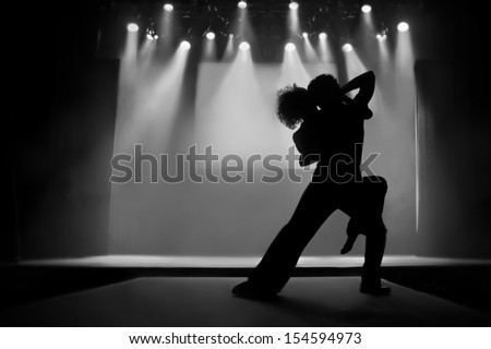 Couple in silhouette dancing on a stage - Black and White picture - stock photo