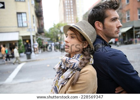 Couple in street leaning back to back - stock photo
