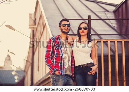 couple in sunglasses standing in the city at sunset. happy weekend - stock photo