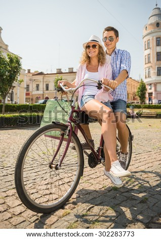 Couple in sunglasses with shopping bags riding on bicycle together on the city street. - stock photo