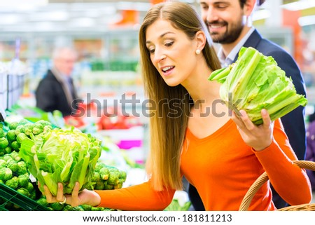 Couple in supermarket at the vegetable shelf shopping for groceries - stock photo