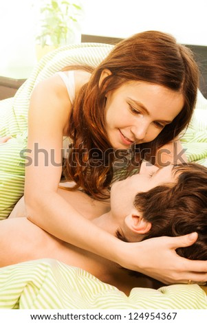 Couple in the bed with wife on top kissing husband - stock photo