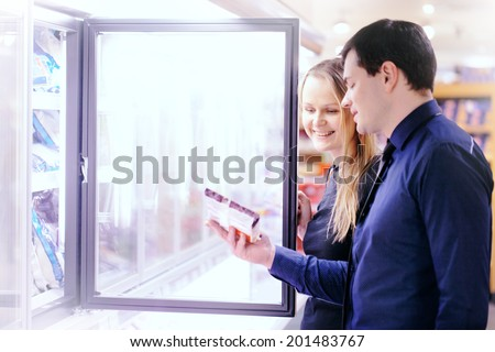 Couple in the frozen goods section of a grocery store picking out food from the freezer - stock photo