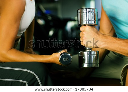 couple in the gym having a workout with dumbbells - stock photo