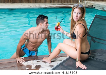 couple in the swimming-pool having a cocktail - stock photo