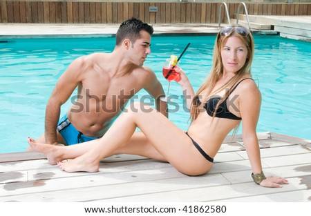 couple in the swimming pool having a cocktail - stock photo