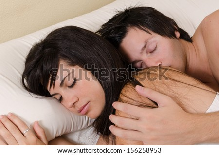 Couple in their 20s relaxed and sleeping in an embrace - stock photo
