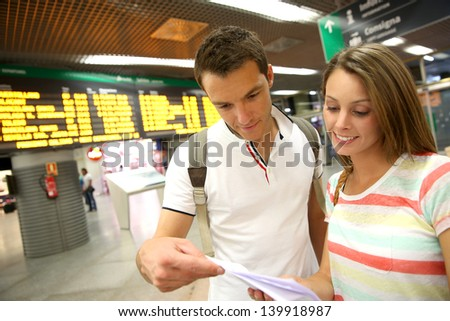 Couple in train station checking trip tickets - stock photo