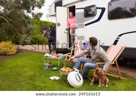 Couple In Van Enjoying Barbeque On Camping Holiday   - stock photo
