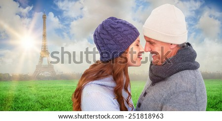 Couple in warm clothing facing each other against eiffel tower - stock photo