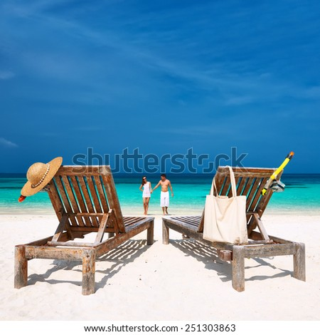 Couple in white walking on a tropical beach at Maldives - stock photo