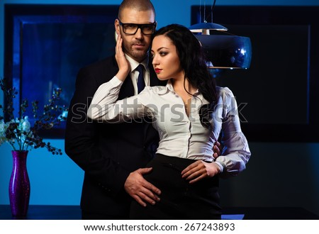 Couple indoors. Sensual brunette and handsome businessman hugging indoors. Office romance concept - stock photo