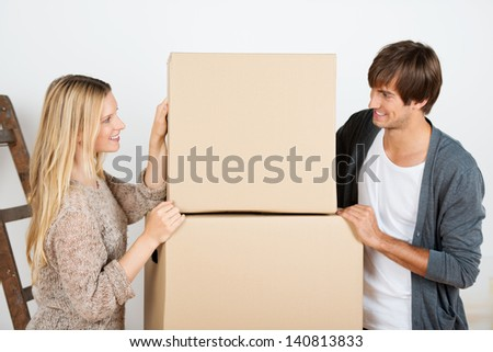 couple is standing beneath a batch of boxes - stock photo