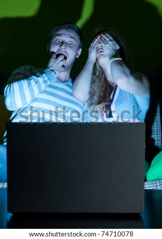 couple is watching scary movie indoors at night - stock photo